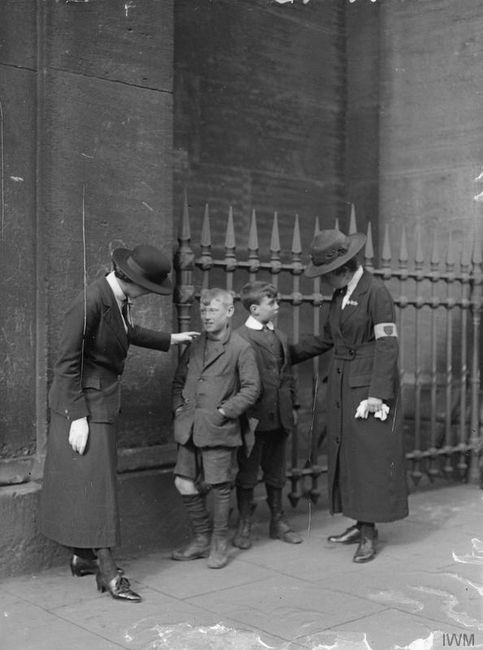 A female police patrol warning small boys outside of Euston Station, 1918. © IWM (Q 31089)
