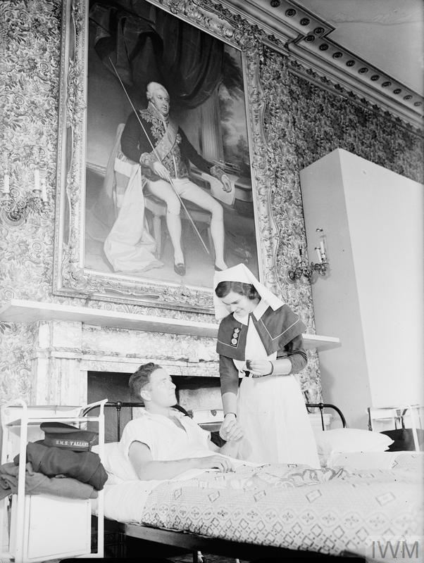 QAIMNS Sister taking the pulse of a patient at Cholmondeley Castle. © IWM (A 11529)