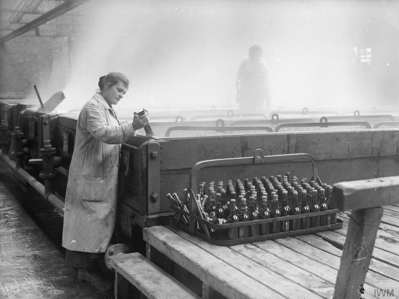 Female worker packing bottles of lager beer in a pasteurizer in a Cheshire brewery, September 1918. © IWM (Q 28328)