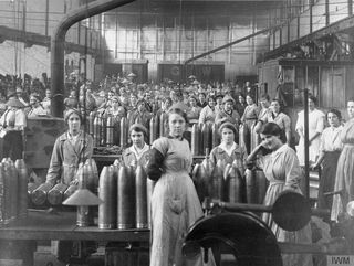 Young female munition workers filling shells in a factory. © IWM (Q 110261)