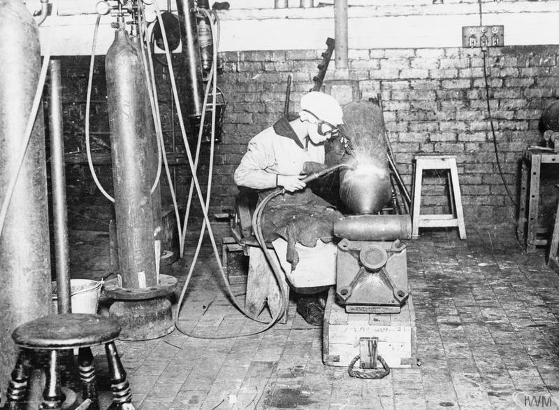 A female munitions worker acetylene welding aerial bombs in a British factory. © IWM (Q 54631)