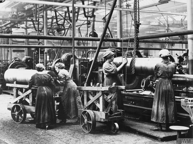 Female munition workers transporting large shells in a factory. © IWM (Q 110230)